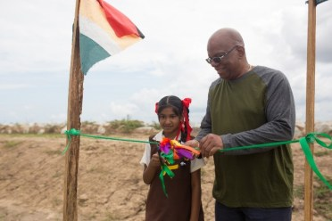 Finance Minister, Hon. Winston Jordan is assisted by a student from Success Primary School to cut the ribbon to officially commission the completed sea defence project.