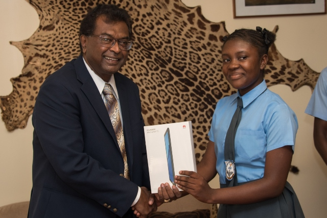 Minister of Public Security Khemraj Ramjattan hands over a electronic tablet to Diamond Secondary School student Saskia Warrick