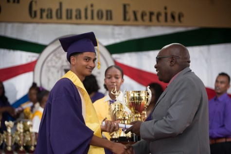 Best Graduating CSEC student, Kumar Persaud receiving prizes from the Chief Education Officer (CEO), Dr. Marcel Hutson.