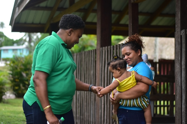 Minister within the Ministry of Communities, with responsibility for Housing, Hon. Annette Ferguson sharing a light moment with a mother and her child.
