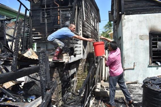 His Worship Pandit Ubraj Narine assisting a fire victim