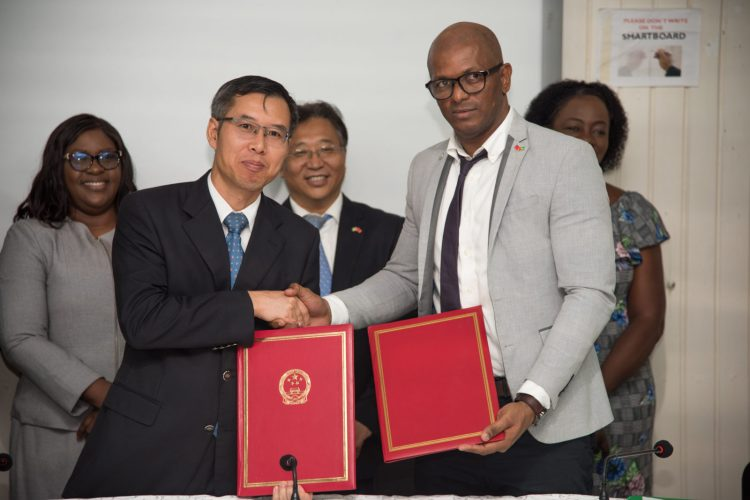 Charge d'affaires Chinese embassy in Guyana Chen Xilai and President of the Guyana Tennis Association, Godfrey Monroe officially handover the agreements (in the back row from left) Dr the Hon. Karen Cummings, Minister of Foreign Affairs, H.E. Cui Jianchun, Ambassador of China to Guyana and Hon. Nicolette Henry, Minister of Education