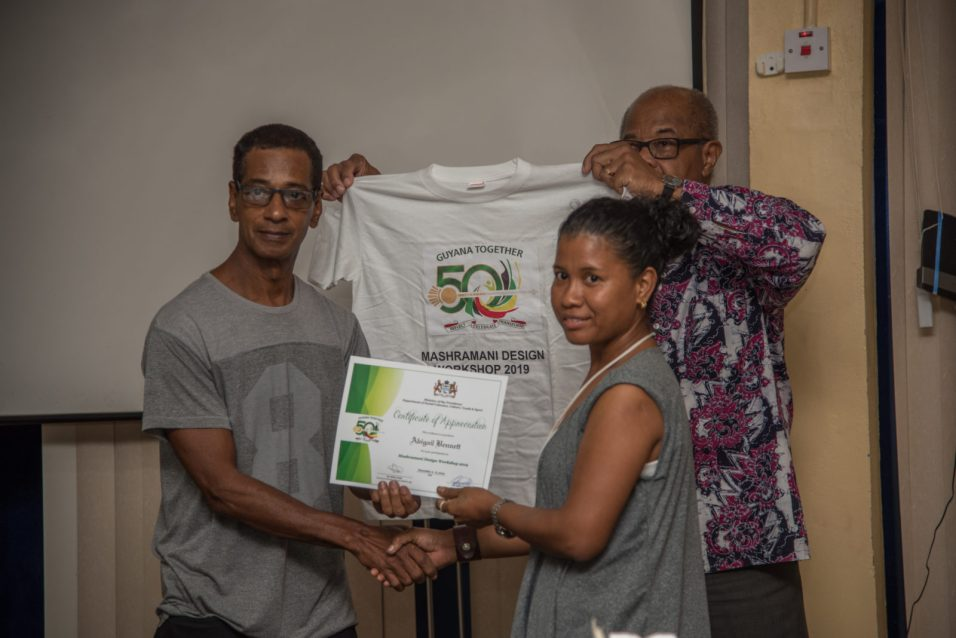 Guyanese Artist, Antonio Butts and Dr. Cambridge presenting awards to a local designer