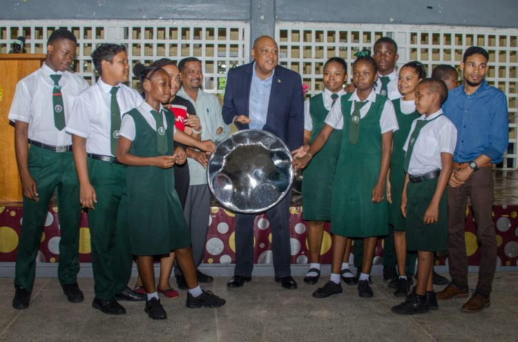 Hon. Raphael Trotman, Minister of Natural Resources, presents two new steelpans to the West Demerara Secondary School