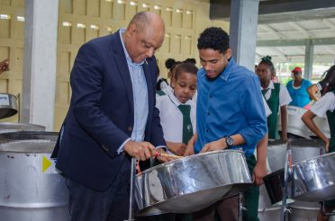 Hon. Raphael Trotman, Minister of Natural Resources, is given an impromptu pan lesson by Music Teacher, Lionel Bishop at the West Demerara Secondary School
