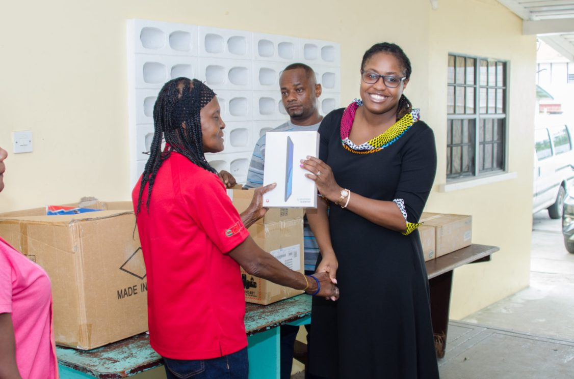 A staff member of the St. John Bosco Boys Orphanage receiving an electronic table from Minister of Public Service Tabitha Sarabo-Halley
