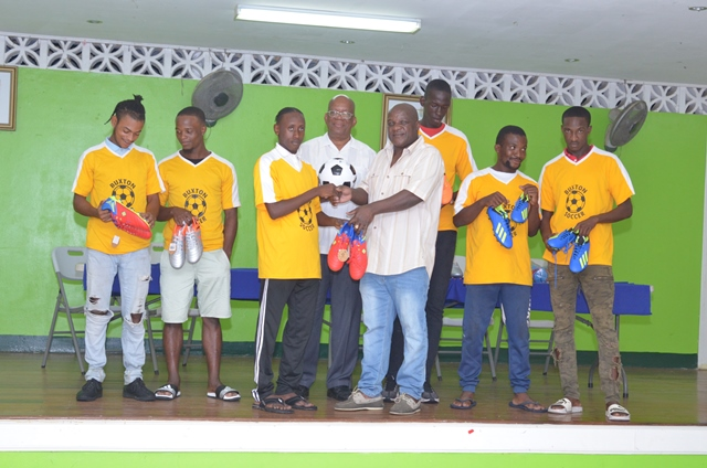 Minister of Finance, Hon. Winston Jordan alongside Businessman Godfrey Harry during the handover of sport gear to members of the Buxton United Sports Club.