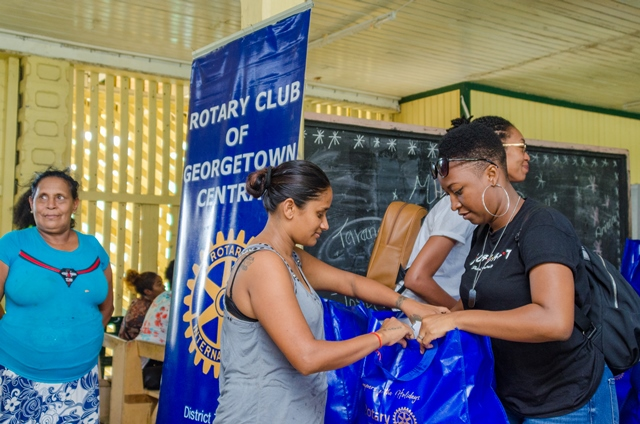 One of the Rotaract members handing over a food hamper to a resident.