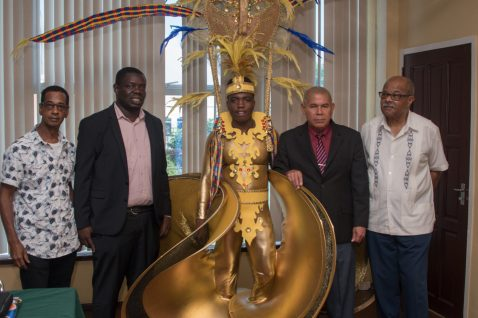 (From left) Antonio Butts, Mashramani Coordinator, Andrew Tyndall, Young model displaying costume, Hon. Minister Dr. Norton and Dr. Cambridge