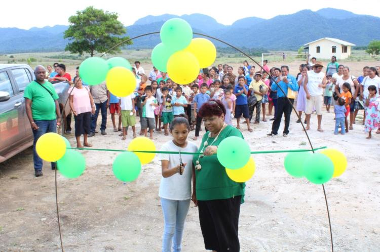Minister of Social Protection, Hon. Amna Ally is assisted by a young girl from the community of Hiawa to cut the ribbon to officially open a multipurpose building.