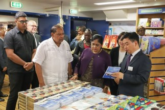 Director Pil-Hun Park shows Prime Minister Nagamootoo and Mrs. Sita Nagamootoo one of the over 6000 types of books on board the Logos Hope.