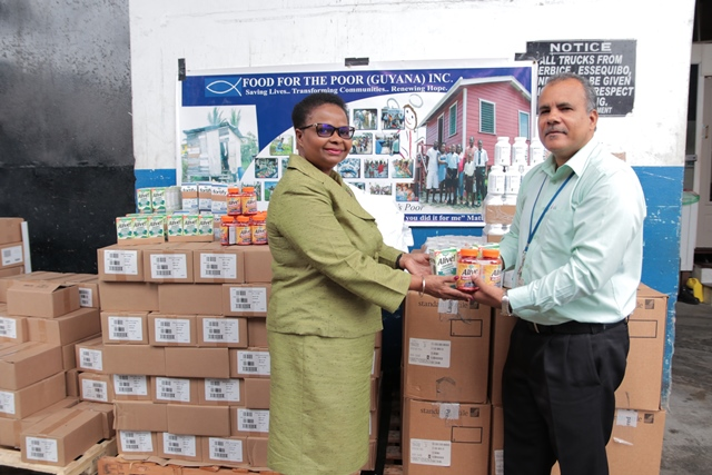 Hon. Volda Lawrence Minister of public health receiving supplements from CEO of Food For The Poor (Guyana) Inc., Kent Vincent