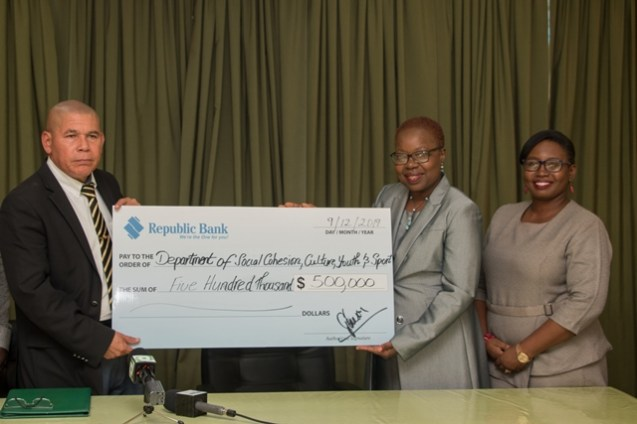 Minister of Social Cohesion Dr. George Norton receives the cheque from Yonnette Greaves, Manager of Information Technology and E-support of Republic Bank. Looking on is Communications and Public Relations Officer, Republic Bank, Jonelle Dummett