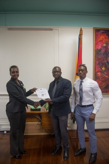 President of the GABBFF Keavon Bess presenting the Bid document to Assistant Director of Sport Melissa Dow Richardson in the presence of Gold Medalist Kerwin Clarke.