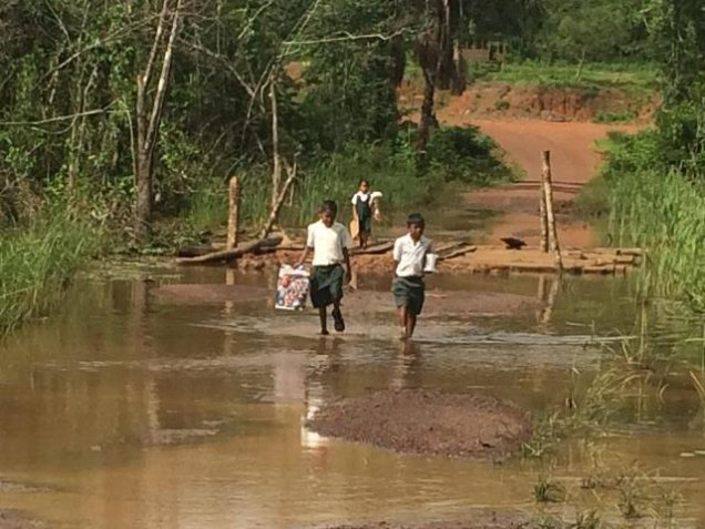 Students walking through the muddy water