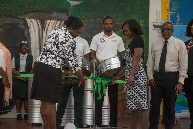 Minister of Education Dr Nicolette Henry cuts the ribbon to official hand over the steel pans to Deputy Headteacher of Mackenzie High School.
