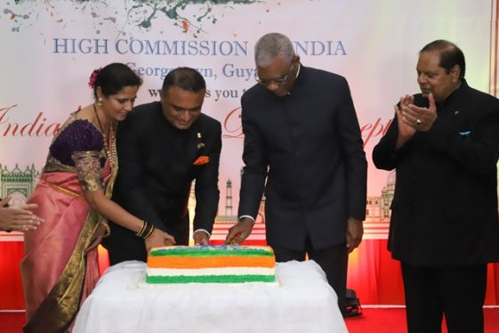 High Commissioner of India to the Republic of Guyana, Dr. K. J. Srinivasa and His Excellency David Granger cut the cake to mark the occasion as the High Commissioner's wife and Prime Minister, Hon. Moses Nagamootoo look on.
