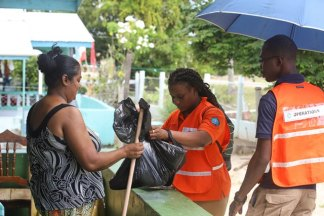 CDC volunteers distributing cleaning supplies to a resident.