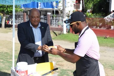 "Minister Raphael Trotman purchases a Macro ""chilli"" hotdog from Wharton."