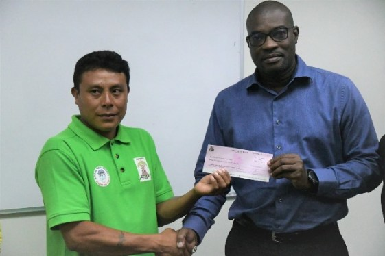 Minister of Public Infrastructure David Patterson presents the cheque to Toshao of Taushida Village Carlon Francis.