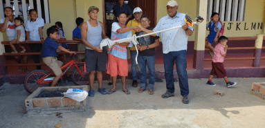 Minister Trotman hands over brush cutter to local football group.