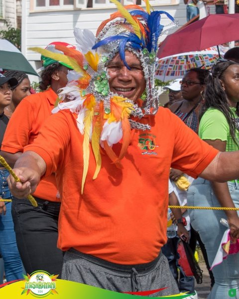Minister of Social Cohesion Dr. the Hon. George Norton enjoys himself as he leads his band down Vlissengen Road.