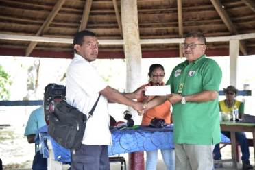 Minister of Indigenous Peoples' Affairs, Hon. Sydney Allicock handing over the cheque to Kendell Francis, Toshao of Paipang.