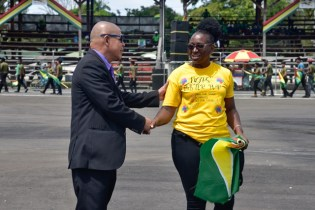 Minister of Social Cohesion, Hon. George Norton speaking with one of the coordinators of the 50th flag raising ceremony.
