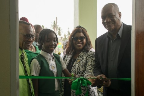 Young Mackenzie High School student assists in cutting of ribbon to the $38.1M edifice.