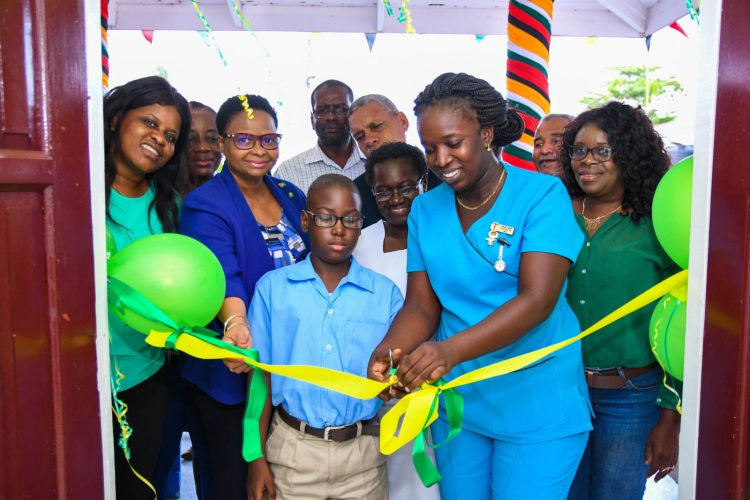 Public Health Minister Hon. Volda Lawrence assists a student of the St. John the Baptist Primary School and Senior Nurse Carrol Samuels to cut the ribbon to officially reopen the expanded A&E unit at the Bartica Hospital
