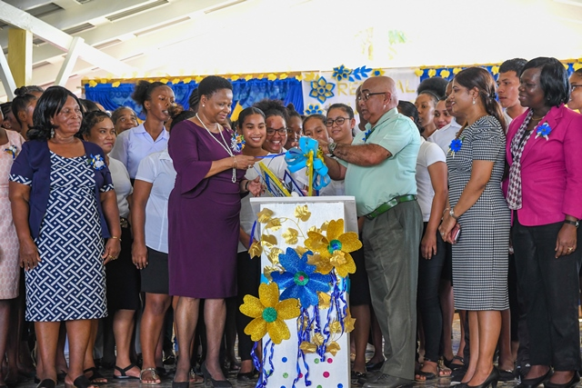 Minister of Public Health Volda Lawrence and Regional Executive Officer, Denis Jaikarran unveils the programme package for the region's inaugural Community Health Workers training programme with Community Health Workers in training, staff of the MoPH and region looking on.