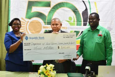 Acting Manager of Marketing and Communications, Republic Bank, Jonelle Dummett (left), hands over cheque to Minister of Social Cohesion, Hon. Dr. George Norton (center) and Mashramani Coordinator, Andrew Tyndall (right).