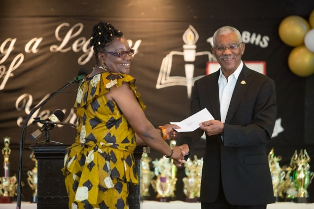 President Granger hands over a cheque of $1M to Principal of the Bishops High School, Marilyn Gibson.