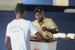 A member of the Guyana Police Force casts his ballot.