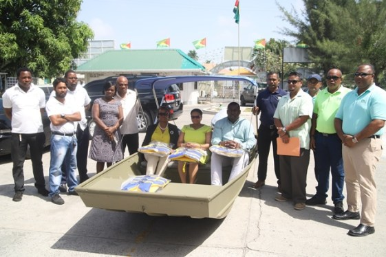 Staff of General Marine Company, the Supplier of the Boat along with IDB Representatives for the MCH Improvement project and staff of the Minister's secretariat (standing alongside the boat) with Director of Primary Healthcare Services, Dr. Ertenisa Hamilton, Minister of Public Health, Volda Lawrence and Regional Health Officer, Dr. Cerdel Mc Watt sit inside the boat.