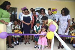 Minister of Public Health Volda Lawrence looks on as Dr. Kittindie Pearson-Boyle and two little ones cut the ribbon to commission the hralth centre at Eccles.