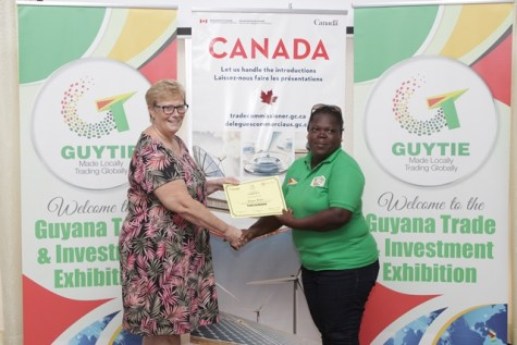 Entrepreneur, Ms. Simone Peters receives a certificate of participation from workshop facilitator Margaret Steeves.