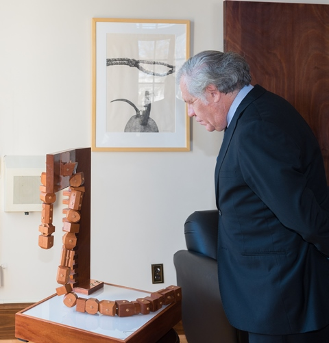 "OAS Secretary-General Luis Almagro observes the sculpture entitled ""Slave Stock and Whip""."