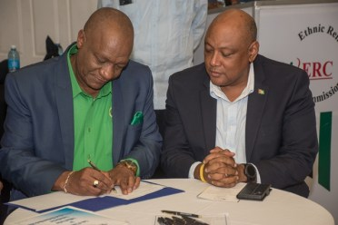 Joseph Harmon and Raphael Trotman (APNU+AFC) signing the Code of Conduct.