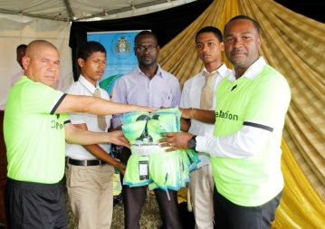 Minister Norton and Mr. Forde handing-over items to the Charlestown Secondary School children.