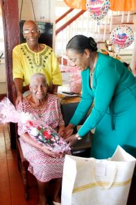 Minister Henry Presenting Mrs. Gravesande with one of her many birthday gifts.