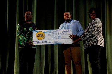 Corporate Communications Officer at Ansa McAL, Mr. Treiston Joseph hands over the sponsorship cheque to Minister Henry and Mrs. Barker-King.