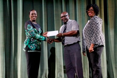 Communications Manager of Banks DIH Ltd, Mr. Troy Peters hands over the sponsorship cheque to Minister Henry and Mrs. Barker-King.