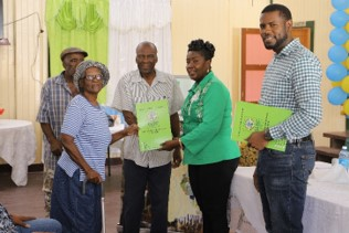 Hon. Valarie Yearwood presents an elderly Kwakwani couple with their land lease.