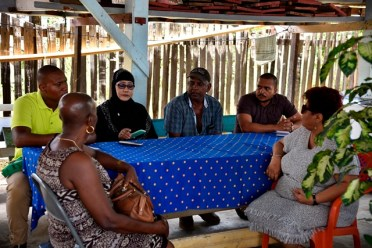 Minister of Social Protection Hon. Amna Ally (right) during the visit to the home of the Azeez family in Bush Lot, Region 5. MP Jennifer Wade is seated extreme left.