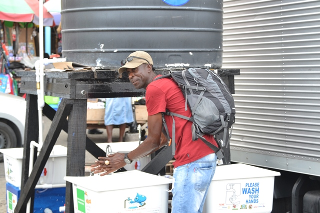 Floyd Alleyne from Uitvlugt, West Bank Demerara' uses the public handwashing station at Stabroek Square.