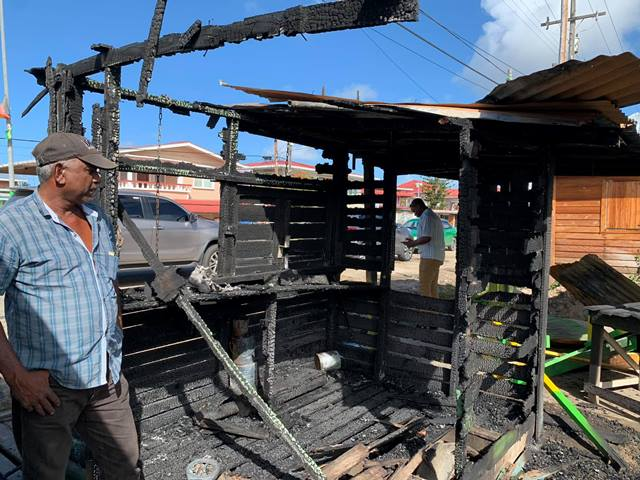 Mr. Azeez assesses the ruins of his butcher's stand destroyed by arson.