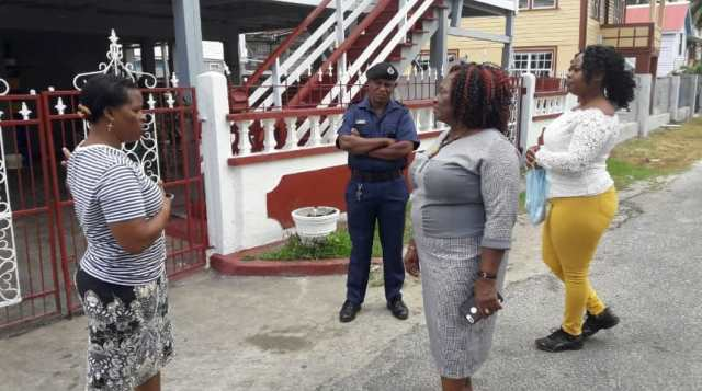 Mayor of New Amsterdam, Her Worship Winifred Haywood along with Constabulary Sergeant Paul Beaton and Councillor Sheeanta Lambert interacting with a resident.