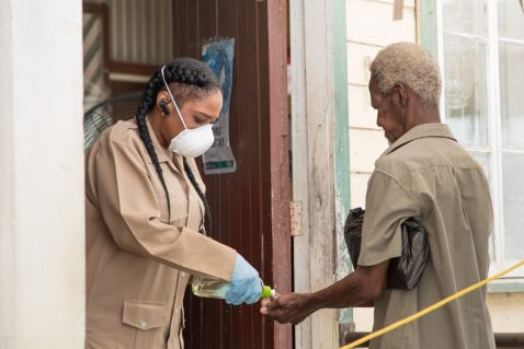 Pensioner being sanitized before entering the post office
