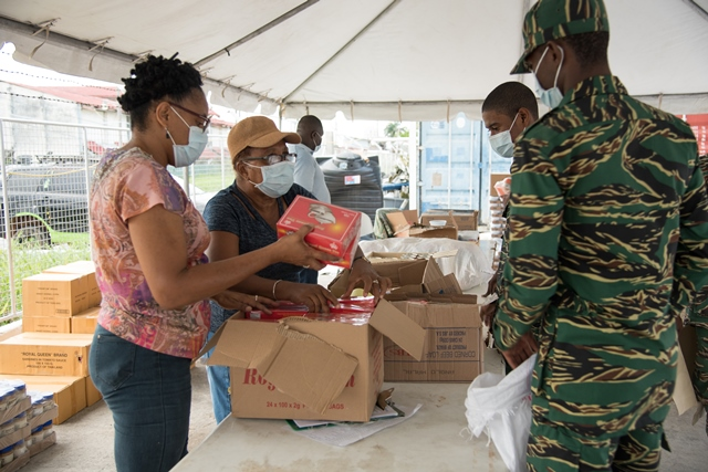 Volunteers and military personnel packaging items